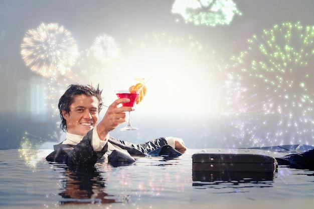 Imagen compuesta de alegre empresario relajándose en una piscina con un cóctel