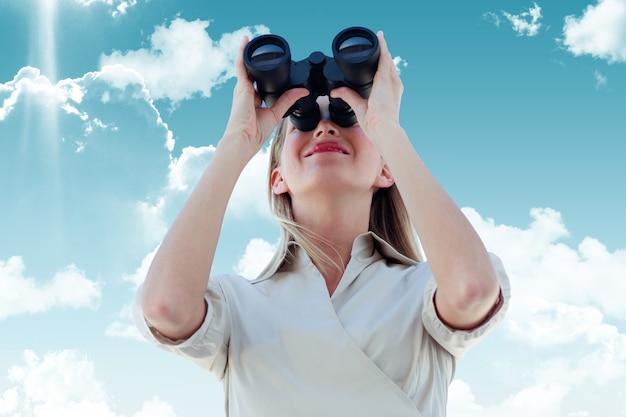 Imagen compuesta de empresaria mirando a través de binoculares