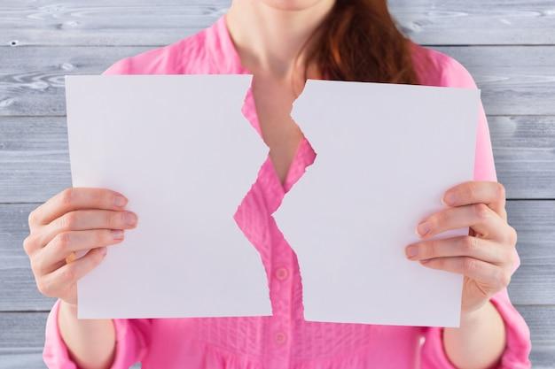 Imagen compuesta de mujer sosteniendo una hoja de papel rasgada
