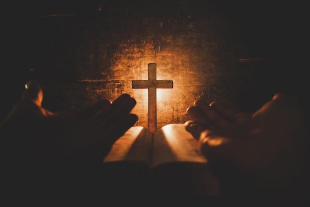 Imagen conceptual centrada en la luz de las velas con la mano del hombre sosteniendo una cruz de madera sobre la biblia y el mundo borroso