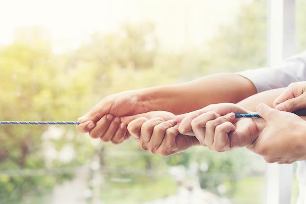 Imagen conceptual del equipo de negocios utilizando una cuerda como elemento del trabajo en equipo.