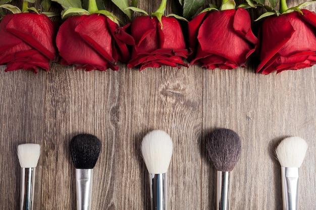 Imagen conceptual de pinceles de maquillaje junto a rosas sobre fondo de madera