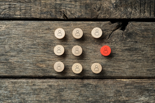 Imagen conceptual de singularidad e individualidad: círculo de corte de madera rojo con el icono de personas destacando entre la multitud de otros.
