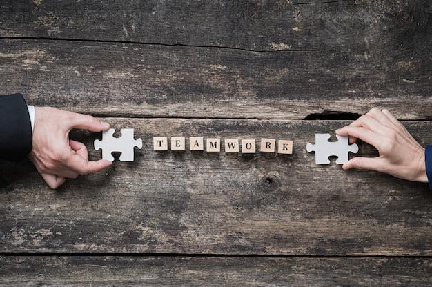 Imagen conceptual de trabajo en equipo y asociación empresarial - manos masculinas y femeninas sosteniendo piezas de un rompecabezas a cada lado de la palabra trabajo en equipo deletreada en cubos de madera.