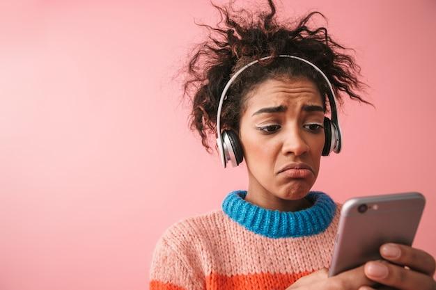 Imagen de conmocionada disgustada hermosa joven africana posando aislado escuchando música con auriculares mediante teléfono móvil.