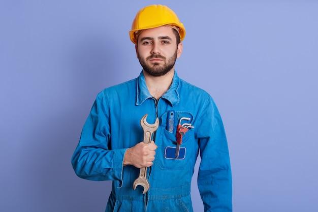 Imagen del constructor joven fuerte confiado que sostiene la llave en una mano, vistiendo el uniforme azul, colocándose aislado sobre la pared azul en estudio. concepto de personas y trabajo.