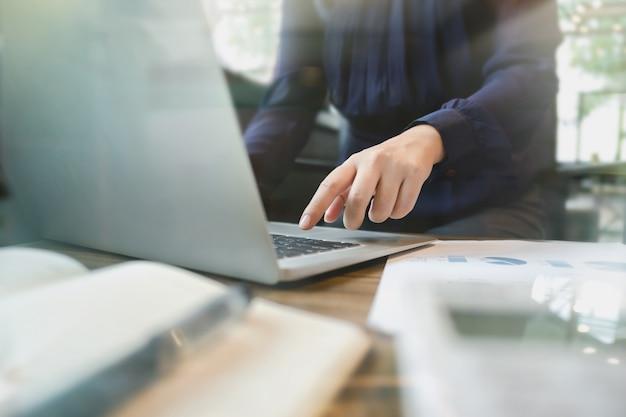 Imagen de contador / inspector financiero calculando sobre datos de inversión con documentos y portátil