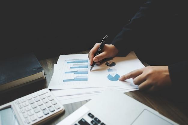 Imagen de contador / inspector financiero cálculo en la inversión de datos con documentos y portátil en la oficina oscura habitación