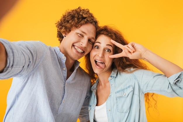 Imagen de contenido pareja hombre y mujer tomando selfie foto mientras muestra el signo de la paz con una sonrisa, aislado sobre fondo amarillo