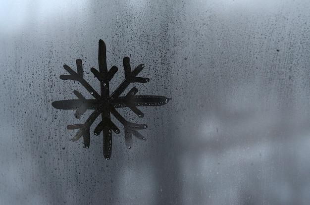La imagen del copo de nieve se dibuja con un dedo en la superficie de una ventana de vidrio empañado