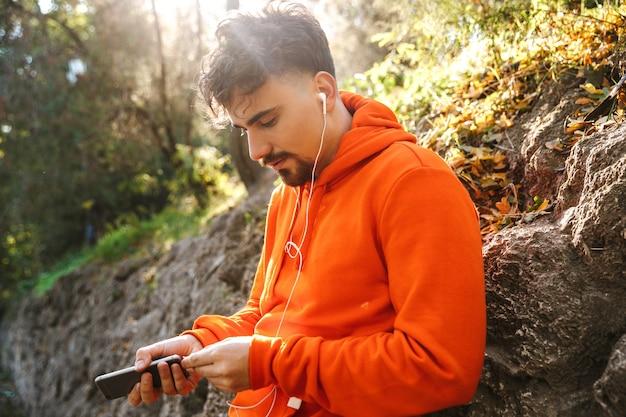 Imagen de corredor de hombre de fitness deportivo joven guapo al aire libre en el parque escuchando música con auriculares mediante teléfono móvil.