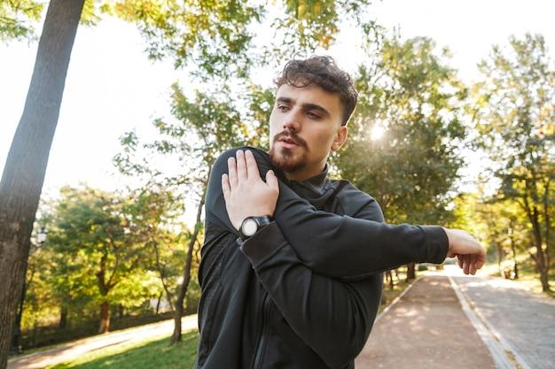 Imagen de corredor de hombre de fitness deportivo joven guapo al aire libre en el parque hacer ejercicios.