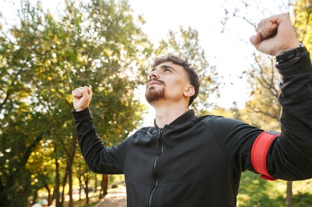 Imagen de corredor de hombre de fitness deportivo joven guapo al aire libre en el parque.