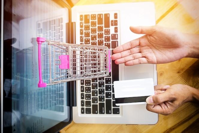 Imagen cosechada de la mujer que introduce la información de la tarjeta y la llave en el teléfono o el ordenador portátil mientras que hace compras en línea.