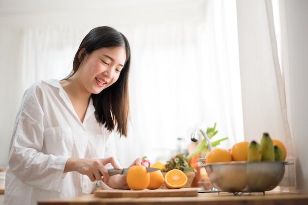 Imagen cosechada de las frutas del corte de la mujer mayor en la cocina. comida sana.