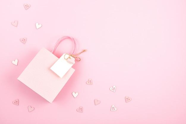 Imagen creativa de bolsa de regalo y caja con etiqueta vacía, corazón y decoración navideña en colores rosa pastel.