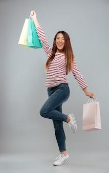 Imagen de cuerpo entero de feliz mujer asiática en suéter alegrarse