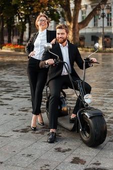 Imagen de cuerpo entero de la feliz pareja de negocios posando con moto