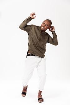 Imagen de cuerpo entero del hombre africano feliz bailando y mirando a otro lado