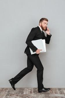 Imagen de cuerpo entero de un hombre barbudo sorprendido en traje