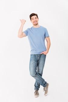 Imagen de cuerpo entero del hombre de buen humor presentando texto o producto con el dedo acusador a un lado en copyspace, aislado sobre la pared blanca