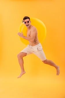 Imagen de cuerpo entero del hombre desnudo feliz en pantalones cortos y gafas de sol