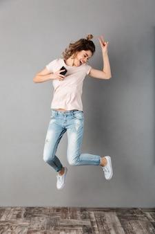 Imagen de cuerpo entero de mujer alegre en camiseta escuchando música desde un teléfono inteligente con auriculares y saltando mientras se divierte y muestra un gesto de paz sobre gris
