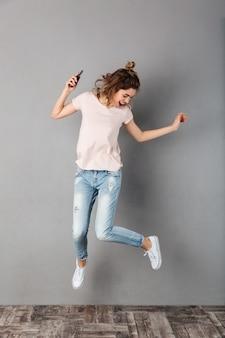 Imagen de cuerpo entero de mujer feliz en camiseta escuchando música desde un teléfono inteligente con auriculares mientras salta y mira hacia abajo sobre gris