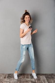 Imagen de cuerpo entero de mujer sonriente en camiseta escuchando música desde un teléfono inteligente con auriculares mientras se divierte sobre fondo gris