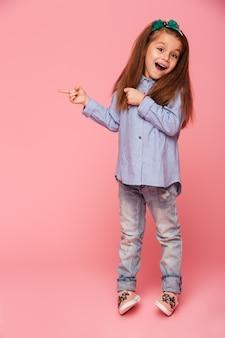 Imagen de cuerpo entero de una niña divertida que gesticula señalando el espacio del dedo índice para copiar su texto o producto