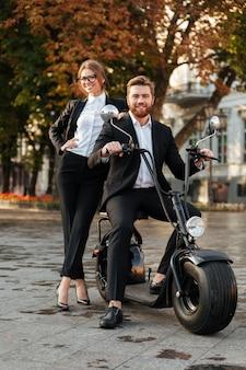 Imagen de cuerpo entero de la sonriente pareja de negocios posando