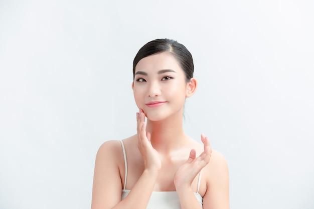 Imagen de cuidado de piel de mujer asiática atractiva aislada en pared blanca