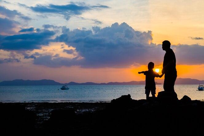 Imagen de la silueta del padre y el hijo en la playa antes del fondo del atardecer
