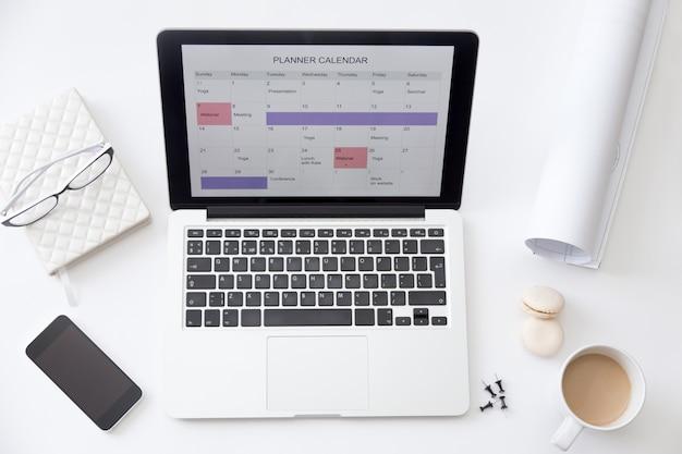 Imagen de vista de ángulo alto de escritorio, planificador de calendario en la computadora portátil