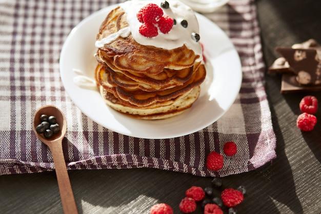 Imagen de un delicioso desayuno para la familia, pancacks con crema agria y bayas frescas, magdalenas decoradas con frambuesas, arándanos