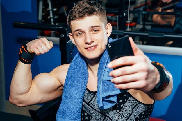 La imagen del deportista joven feliz que se sienta en gimnasio y hace el selfie.