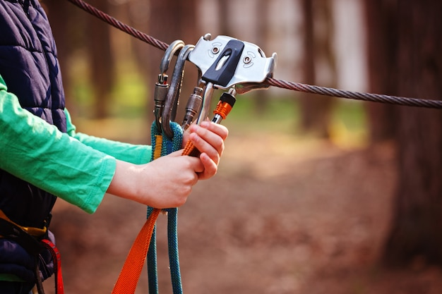 Imagen deportiva de escalada de un mosquetón en una cuerda de metal en un bosque