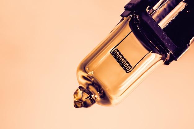 Imagen de detalle de la bombilla de haz sumergido con filamento de cerca con espacio de copia con tono naranja y magenta.