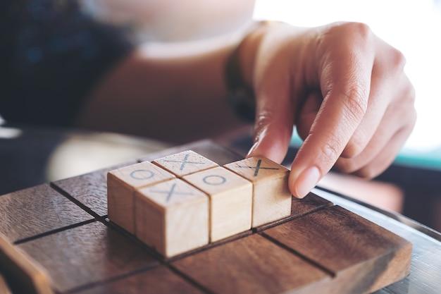Imagen de detalle de personas jugando al juego de madera tic tac toe o juego ox