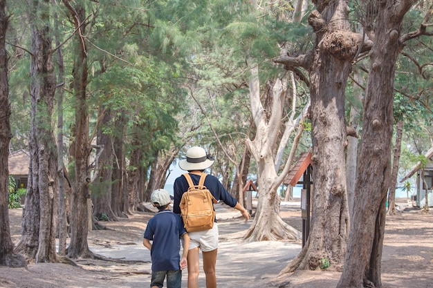 La imagen detrás de madre e hijo caminando sandwalk carretera con árboles cubiertos fondo mar en el parque nacional de la cueva phraya nakhon, prachuap khiri khan, tailandia.
