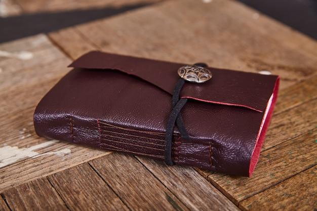 Imagen de diario de cuero púrpura detalle cerrado sobre tableros de madera