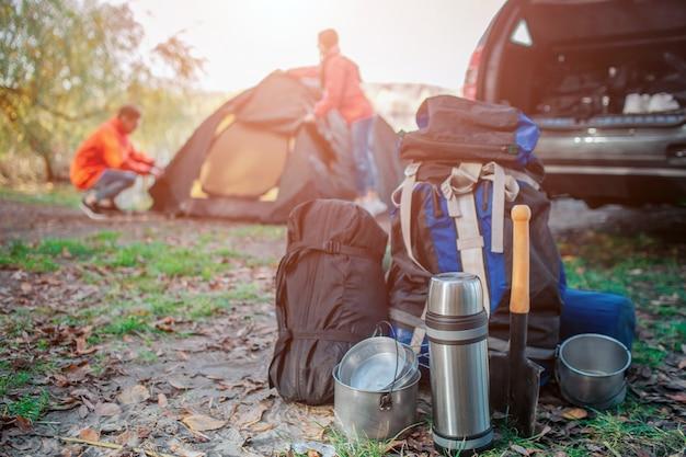 Imagen de diferentes equipos de expedición. hay mochila con carimate, saco de dormir y vajilla. joven y mujer están empacando carpa. ellos estan en el auto.