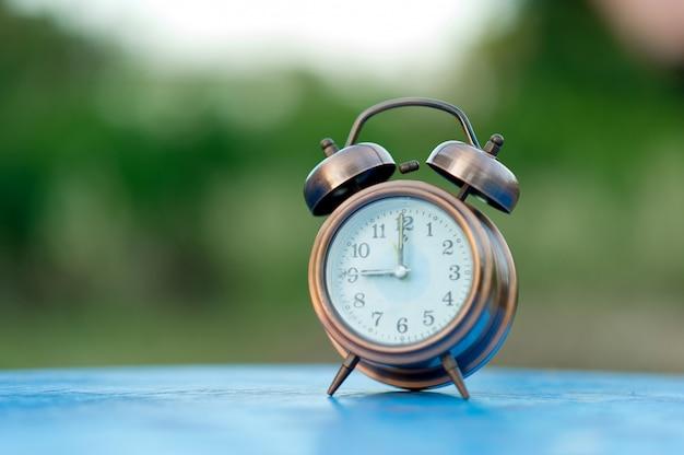 Imagen dorada del reloj de alarma colocada en una mesa azul, fondo verde. concepto puntual con espacio de copia.