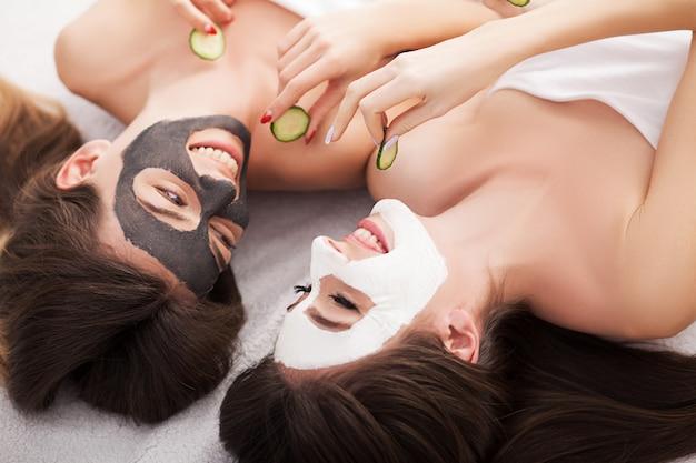 Una imagen de dos amigas relajantes con máscaras faciales sobre fondo blanco.