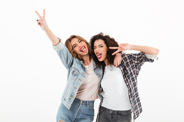 Imagen de dos chicas juguetonas de pie juntas y mostrando gestos de paz sobre una pared blanca