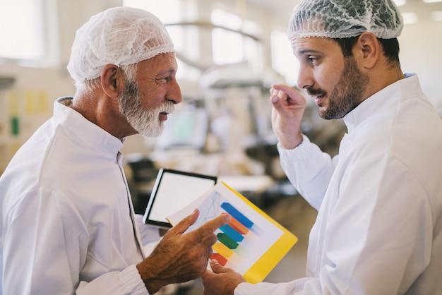 Imagen de dos compañeros de trabajo masculinos en ropa esterilizada hablando de planes de negocios. de pie en la luminosa sala de la fábrica y hablando sobre el histograma de ventas del mes actual.