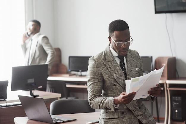 La imagen de dos jóvenes empresarios afroamericanos que interactúan en una reunión en la oficina