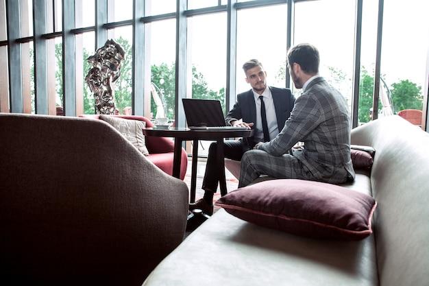 Imagen de dos jóvenes empresarios con touchpad en reunión.