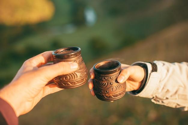 Imagen de dos manos sosteniendo dos tazas de bebida caliente en la naturaleza por la mañana
