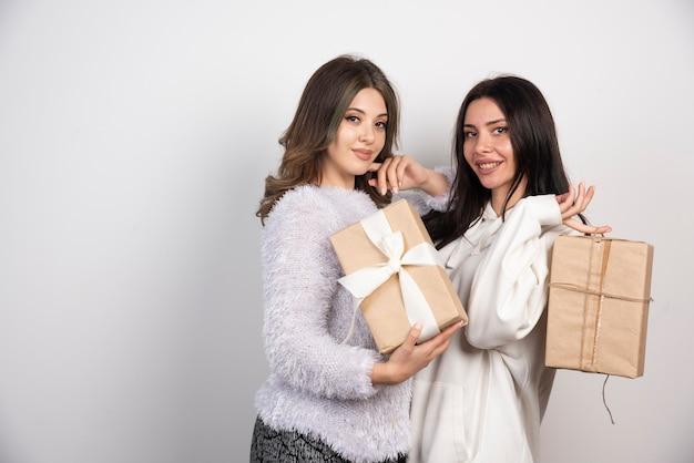 Imagen de dos mejores amigos parados juntos y sosteniendo cajas de regalo.